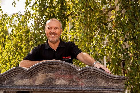 Andreas Mittlböck lehnt auf einem Grabstein und lächelt freundlich in die Kamera