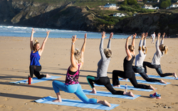 Group yoga on the beach Cornwall Surf Yoga Retreat Wild Free