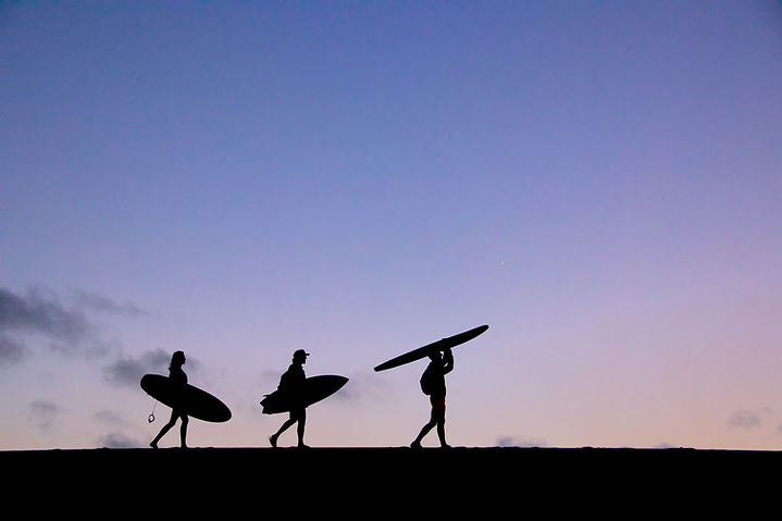 Silhoutted surfers walking across a sand dune