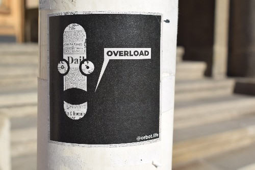 sticker on a lampost of a robot head saying overload