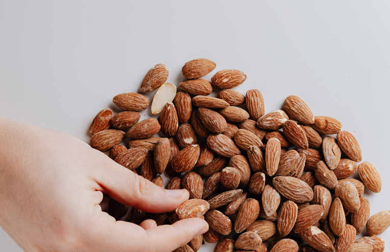 crop-person-taking-almond-nut-from-white