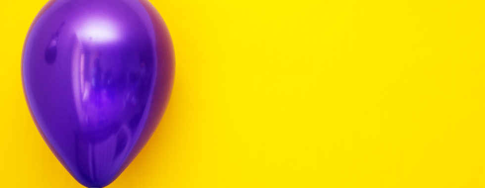 purple-balloon-against-yellow-background