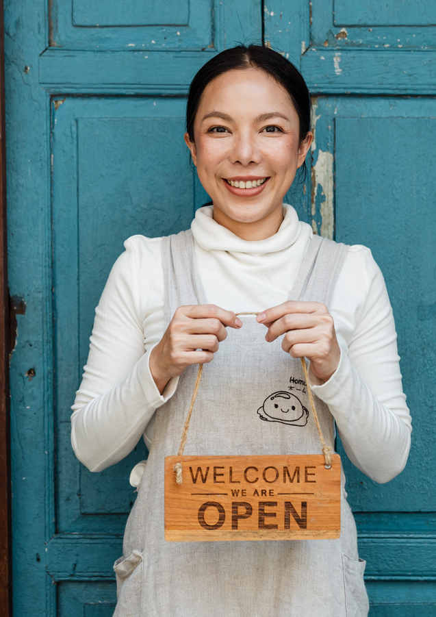 ethnic-female-cafe-owner-showing-welcome