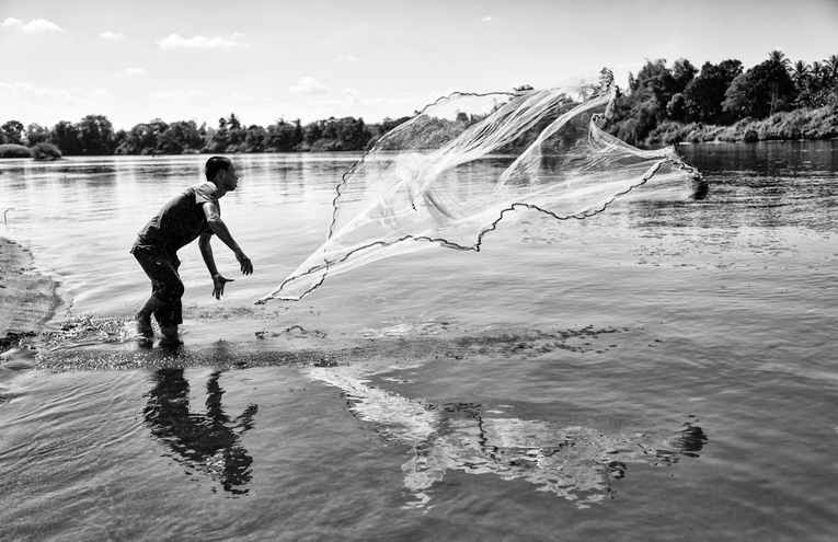 grayscale-photo-of-man-throwing-a-fishin