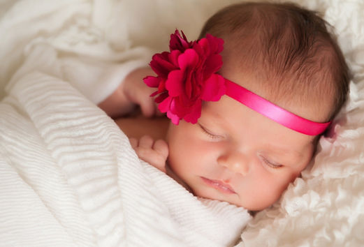 sleeping baby with a red flower hairband