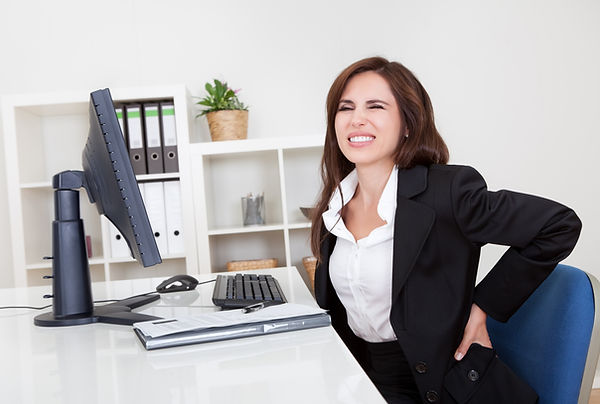 Young businesswoman having back pain whi