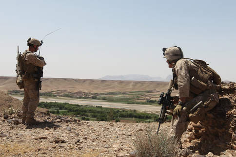 Two Marines look over a ridge after a firefight