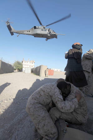 Corpsmen protects baby while helicopter passes over for medical evacuation