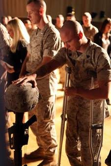 Marine touches helmet of friend killed in action during a memorial ceremony once the unit returned home