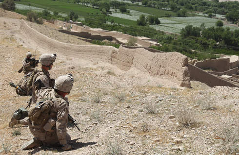 Marines kneel while taking enemy fire