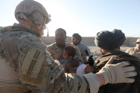 Corpsman holds baby before medical evacuation