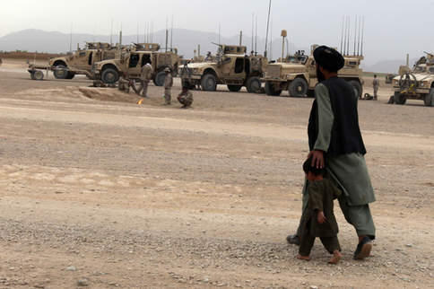 Father and son walk pass Marine vehicles