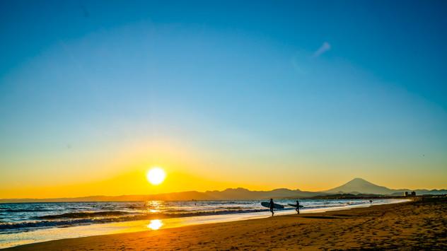 夕日の中の親子サーファー