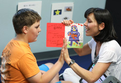 Speech therapist and child are smiling and read a book together