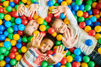 Above view portrait of three happy little kids in a ball pit