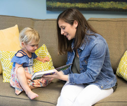 Speech therapist reads a book to a young girl, sitting on a couch