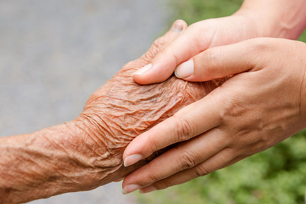 Elderly hand holding young hand