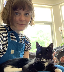 A woman in dungarees with a cat on her lap