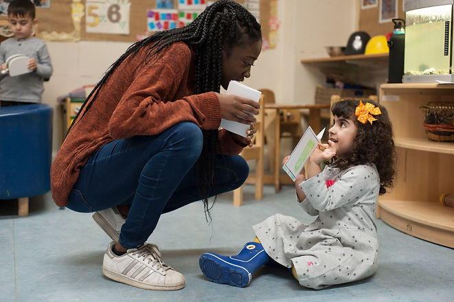A woman is crouching down to a toddler, as they talk about storycards they are both holding. In the background is a nursary with another toddler holding a toy.