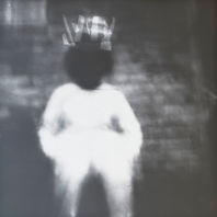 A blurry black and white image of a figure in white. Their face has been blurred out.
