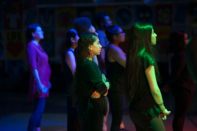 8 young people are facing the right. Two are in the foreground and lit green. Those in the background are lit blue. They are performing.
