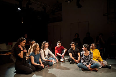 Group of young people sat on a theatre floor.jpg
