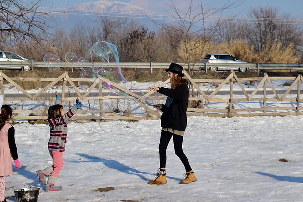 A young woman is standing in the snow creating giant bubbles. A young girl runs towards the bubble.