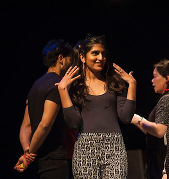 A young woman is in the foreground, she waves her hands at her face, smiling. Behind her other people are talking.