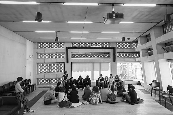 A black and white picture of a group of young people sitting on sofas in the middle distance. On the floor facing them are a group of adults.