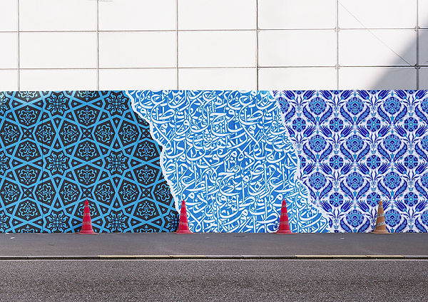 A wall covered in street art. The art is blue and full of repetitative patterns. In front of the wall are orange hazzard street cones.