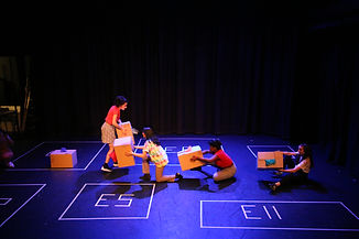Four young women on stage, each holds a carboard box. There are squares taped on the floor with different postcodes taped in each.