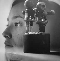 A black and white photo of two clown toys in the foreground, in the back ground the side profile of a woman staring out to the side