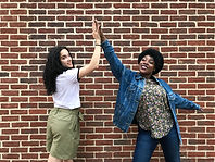 Two young women look at the camera while they high five in the air between them. Behind them is a brick wall.