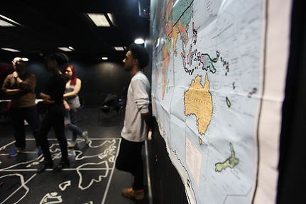 A young man leans against a wall which has a map of the world hung on it. One the floor is a map mad of masking tape. Other young people are in the background.