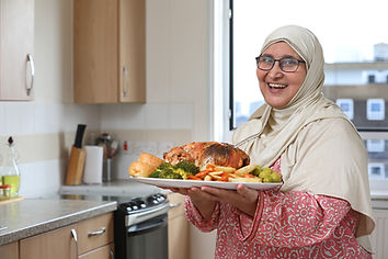 A woman wearing a hijab holding a roast dinner smiling at the camera