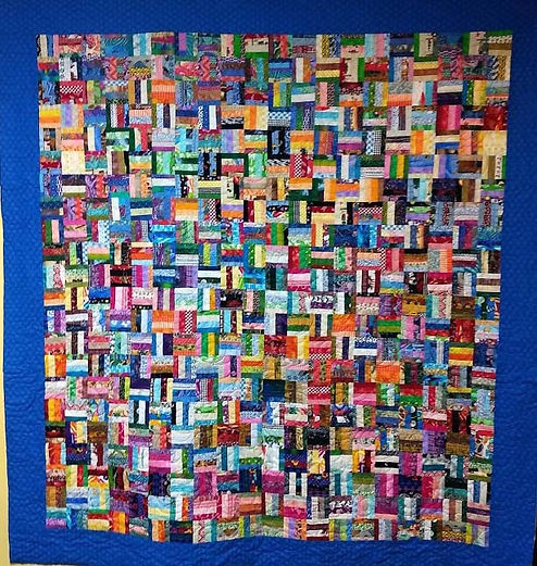 very colorful scrappy quilt with edge to