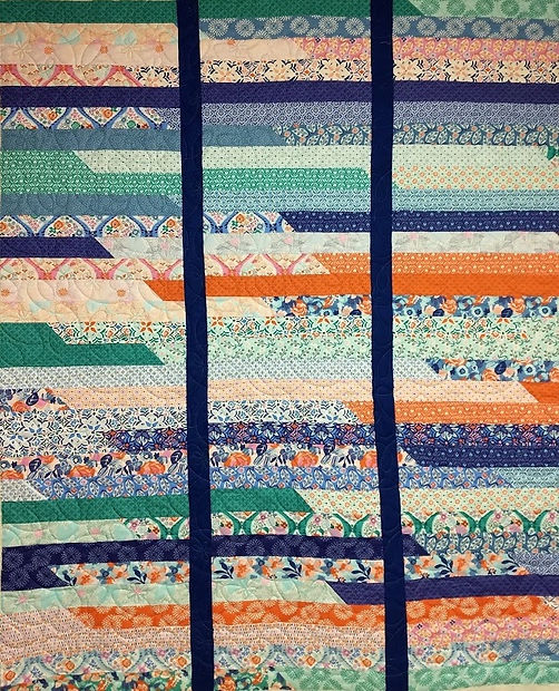Jelly Roll race quilt with Daisy on a St