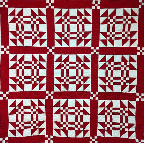 Red and white quilt with longarm quiltin