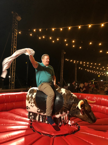 Guy riding PBR Mechanical Bull from By the Horns Mechanical Bull Rental Delaware Pennsylvania Maryland