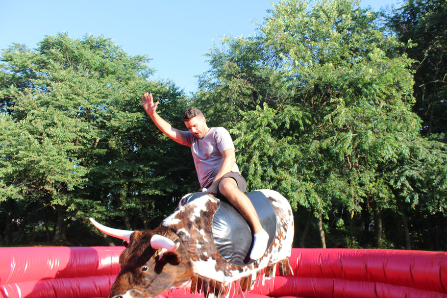 Man riding PBR Mechanical Bull from By the Horns Mechanical Bull Rental Delaware Pennsylvania Maryland
