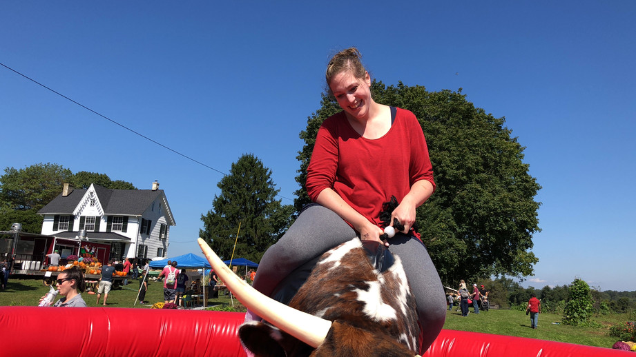 Woman riding PBR Mechanical Bull from By the Horns Mechanical Bull Rental Delaware Pennsylvania Maryland