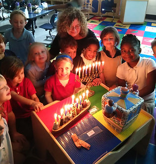 Susan with kindergarten students around Chanukah menorah