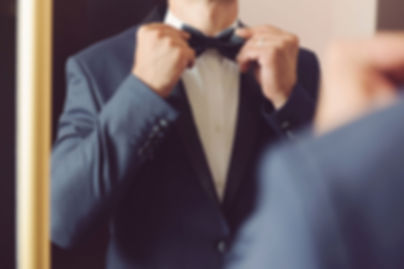 Man standing in front of a mirror in a tuxedo suit, fixing his bow tie.