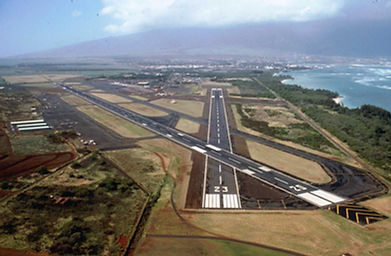 Kahului Airport looking west.  Runway 5-23 (5000') is in the foreground.  Runway 2-20 (7000') intersects Runway 5.  The beach in the right foreground is the world-famous Kanaha beach park.