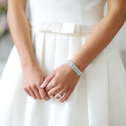 bride wearing silver wedding bracelet and engagement ring