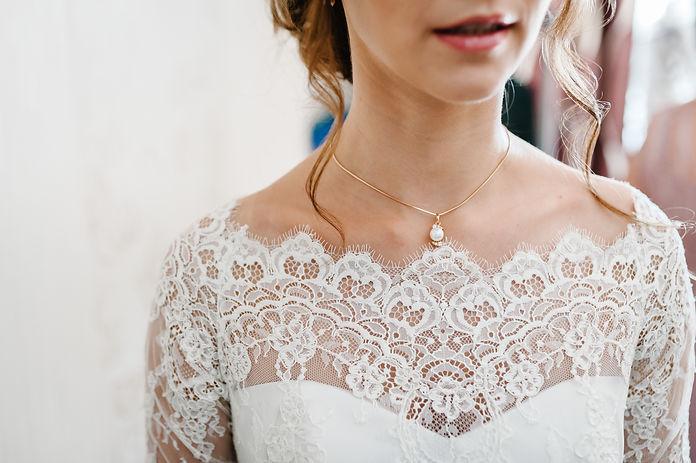 bride wedding dress neckline with gold necklace