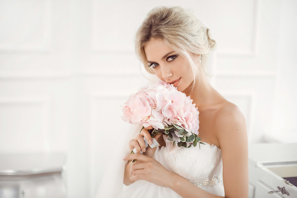 pretty bride with bridal jewellrey holding pink bouquet of flowers