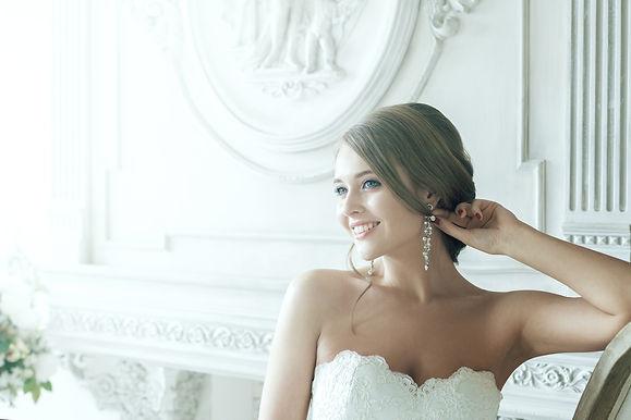 beautiful bride holding elegant wedding earrings