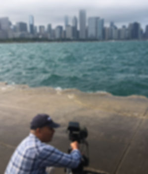 A man is crouced down holding a camera filming the city skyline from across a body of water.