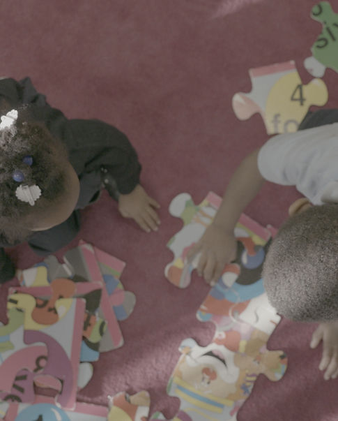 Overhead shot of two children putting a puzzle together.